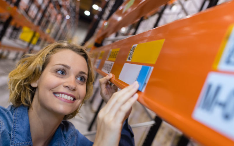 happy warehouse worker putting prices on shelves